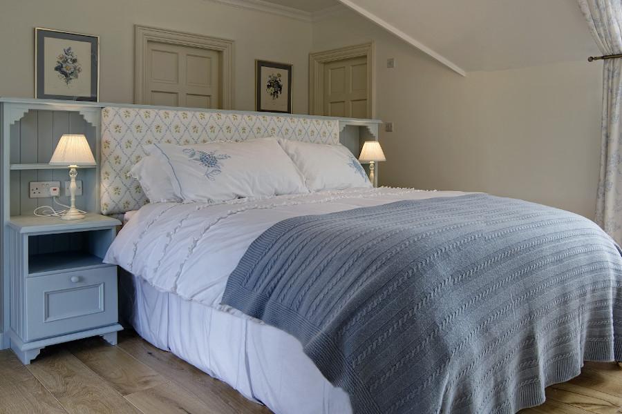 Nowoczesna przytulna sypialnia z tapicerowanym łóżkiem - lampy